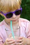 Barnet i solglasögon som dricker choklad, mjölkar Royaltyfri Foto