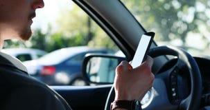 Barnet ilar den attraktiva affärsmannen som använder smartphonen i bilen, stads- stadsbakgrund lager videofilmer