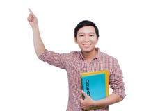 Barnet ilar den lyckliga studenten med böcker som pekar på kopieringsutrymme royaltyfri fotografi