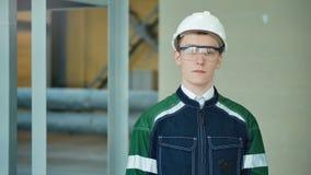 Barnet iscensätter den bärande skyddande hjälmen som poserar se kameran på den moderna fabriken lager videofilmer