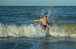 barnet kasta sig över vågorna av det krabba havet Fotografering för Bildbyråer