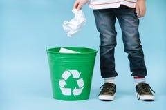 Barnet kastar skrynkligt papper i återvinningfack arkivfoton
