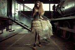 Barnet klädde kvinnan i den tomma järnvägsstationen Arkivbilder