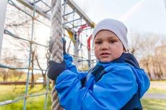 Barnet klamra sig fast intill repet i lekplatsen för barn` s royaltyfri foto