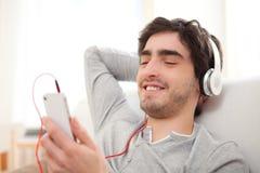 Barnet kopplade av listenning musik för man i soffan royaltyfria bilder