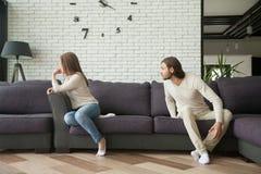 Barnet kopplar ihop att argumentera sammanträde på soffan, mannen som ropar på kvinnan Royaltyfri Foto