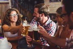 Barnet kopplar ihop att dricka öl och att skratta tillsammans på stången royaltyfri fotografi