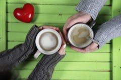 Barnet kopplar ihop att dricka varmt kaffe på trätabellen på ett datum royaltyfri foto