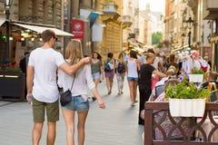 Barnet kopplar ihop att gå ner den Vaci gatan i Budapest arkivbild