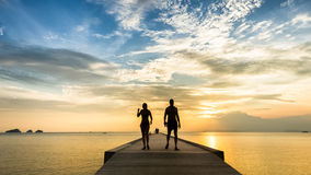 Barnet kopplar ihop att gå på pir i havet på solnedgången Fotografering för Bildbyråer