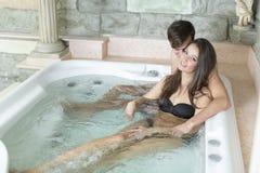 Barnet kopplar ihop att koppla av i det varmt badar Royaltyfri Bild