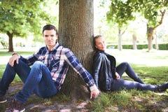 Barnet kopplar ihop att koppla av i skuggan av ett träd royaltyfria foton