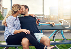 Barnet kopplar ihop att koppla av på en bänk som tycker om en kyss royaltyfri bild