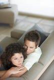 Barnet kopplar ihop att koppla av på soffan Fotografering för Bildbyråer