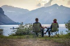 Barnet kopplar ihop att koppla av vid pilbåge sjön i Alberta, Kanada Fotografering för Bildbyråer