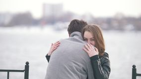Barnet kopplar ihop att krama på bakgrunden på kusten av floden arkivfilmer
