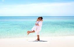 Barnet kopplar ihop att krama på en bedöva tropisk strand Arkivbild