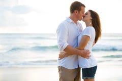 Barnet kopplar ihop att kyssa på stranden på solnedgången Fotografering för Bildbyråer