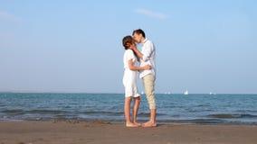 Barnet kopplar ihop att kyssa tillsammans på den soliga stranden arkivfilmer