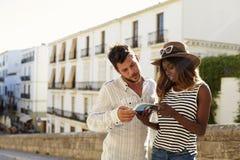 Barnet kopplar ihop att läsa upp en resehandbok, midja, Ibiza, Spanien royaltyfria foton