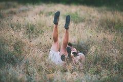 Barnet kopplar ihop att ligga i gräs som sträcker upp deras ben royaltyfri foto