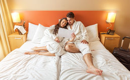 Barnet kopplar ihop att ligga i sängen av ett hotellrum Arkivbilder