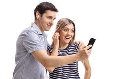 Barnet kopplar ihop att lyssna till musik på en telefon Royaltyfri Bild