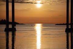 Barnet kopplar ihop att paddla ut till havet på natten royaltyfri fotografi