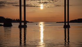 Barnet kopplar ihop att paddla ut till havet på natten Fotografering för Bildbyråer