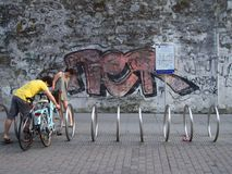 Barnet kopplar ihop att parkera deras cyklar i stad på en cykelkugge framme av en grafittivägg royaltyfria foton