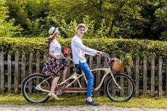 Barnet kopplar ihop att rida en cykeltandemcykel i parkera Mot bakgrunden av staketet från trädet Arkivfoton