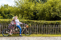 Barnet kopplar ihop att rida en cykeltandemcykel i parkera Mot bakgrunden av staketet från trädet Royaltyfria Foton