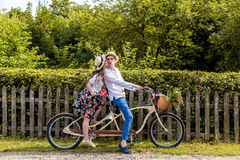 Barnet kopplar ihop att rida en cykeltandemcykel i parkera Mot bakgrunden av staketet från trädet Royaltyfri Fotografi