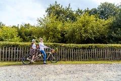 Barnet kopplar ihop att rida en cykeltandemcykel i parkera Mot bakgrunden av staketet från trädet Royaltyfri Foto