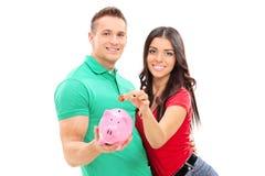 Barnet kopplar ihop att sätta in pengar in i en piggybank Fotografering för Bildbyråer
