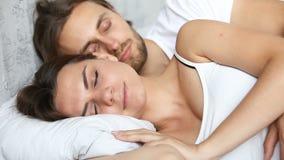Barnet kopplar ihop att sova i säng, liggande omfamna på vit linne arkivfilmer