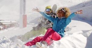 Barnet kopplar ihop att spela i snön på en skidasemesterort arkivfilmer