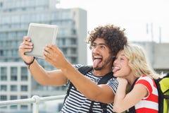 Barnet kopplar ihop att ta en selfie med den digitala minnestavlan Arkivfoton