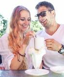 Barnet kopplar ihop att tycka om kaffe på ett gatakafé Royaltyfri Bild