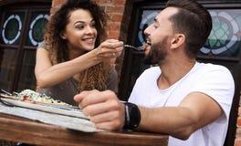 Barnet kopplar ihop att tycka om kaffe på ett gatakafé och att skratta Royaltyfri Fotografi