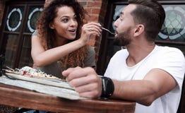 Barnet kopplar ihop att tycka om kaffe på ett gatakafé och att skratta Arkivbild