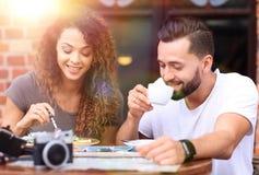 Barnet kopplar ihop att tycka om kaffe på ett gatakafé och att skratta Arkivbilder