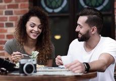 Barnet kopplar ihop att tycka om kaffe på ett gatakafé och att skratta Royaltyfri Bild