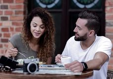 Barnet kopplar ihop att tycka om kaffe på ett gatakafé och att skratta Arkivfoton