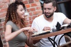 Barnet kopplar ihop att tycka om kaffe på ett gatakafé och att skratta Royaltyfri Foto