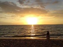 Barnet kopplar ihop att tycka om solnedgången på stranden Fotografering för Bildbyråer