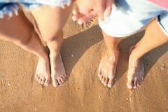 Barnet kopplar ihop att vila tillsammans på stranden, bästa sikt royaltyfri bild