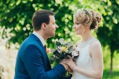 Barnet kopplar ihop, bruden och brudgummen med blommor i skogen royaltyfria bilder