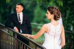 Barnet kopplar ihop, bruden och brudgummen som går och tycker om deras bröllopdag solsken Sommar Royaltyfria Bilder
