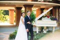 Barnet kopplar ihop, bruden och brudgummen som går och tycker om deras bröllopdag solsken Sommar Royaltyfria Foton